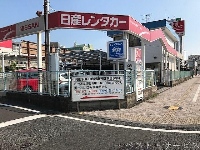 日産レンタカーのフェンスの角に ←で「岡山駅西口自転車専用駐輪場(有料)」という看板があります