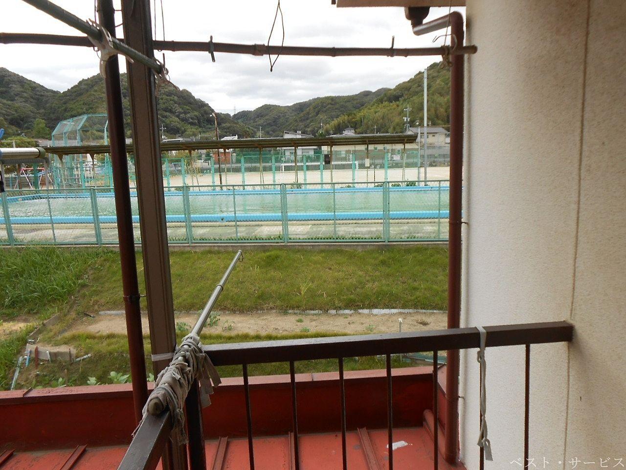 ベランダから灘崎町小学校の運動場(プール)が見える